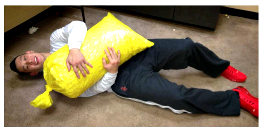 JEREMY LIN LAYING ON FLOOR HUGGING YELLOW TRASH BAG