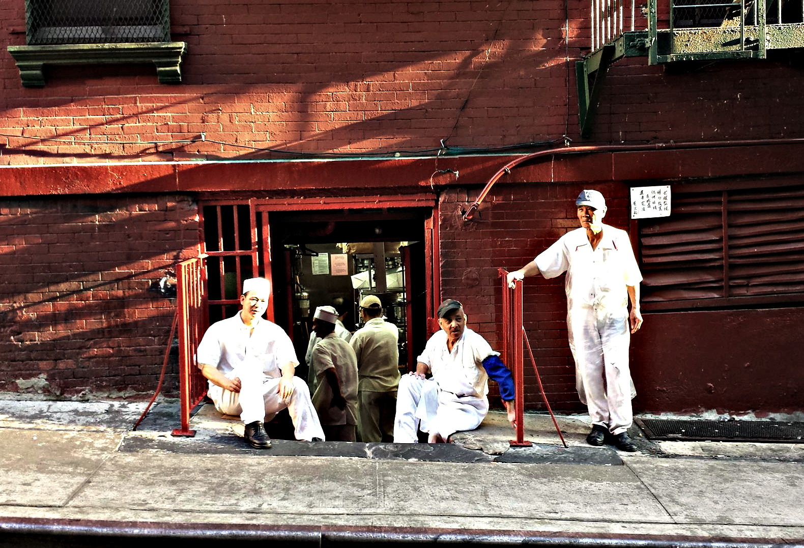 Chinese restaurant workers relaxing out back on Mosco Street